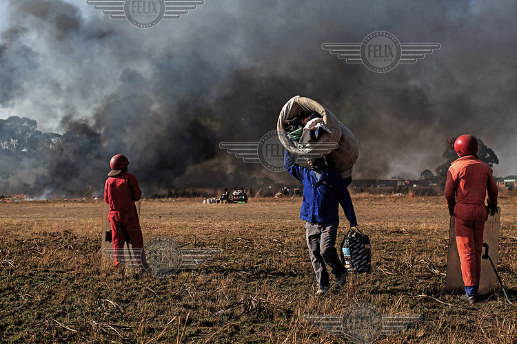 A man carries a few of his possessions as the Red Ants evict residents and destroy an informal settlement near Pomona. <br />The Red Ants are a controversial private security company often hired to clear squatters from land and so-called 'hijacked' properties.