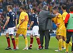 Macedonian manager Mirsad Jonuz holds back his player Veliche Shumulikoski after he pushed Alan Hutton