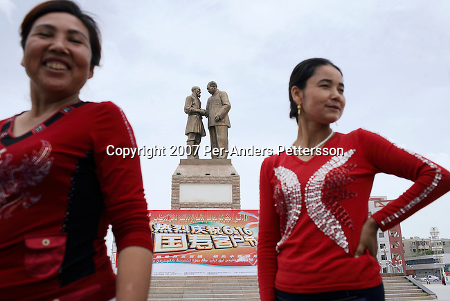 KHOTAN, CHINA - JUNE 18: Chinese tourists pose for photographs next to a Mao statue on June 18, 2007 in central Khotan, China. A group of women traveled on the Silk Road from Aksu to Kashgar. (Photo by Per-Anders Pettersson)...