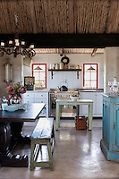 A country style kitchen with a beamed ceiling and concrete floor. The room is furnished with white fitted units and a stainless steel range oven. A wooden table and bench provide an eating area.
