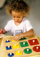 Young girl age 5 practicing with blocks to learn shapes in schoo