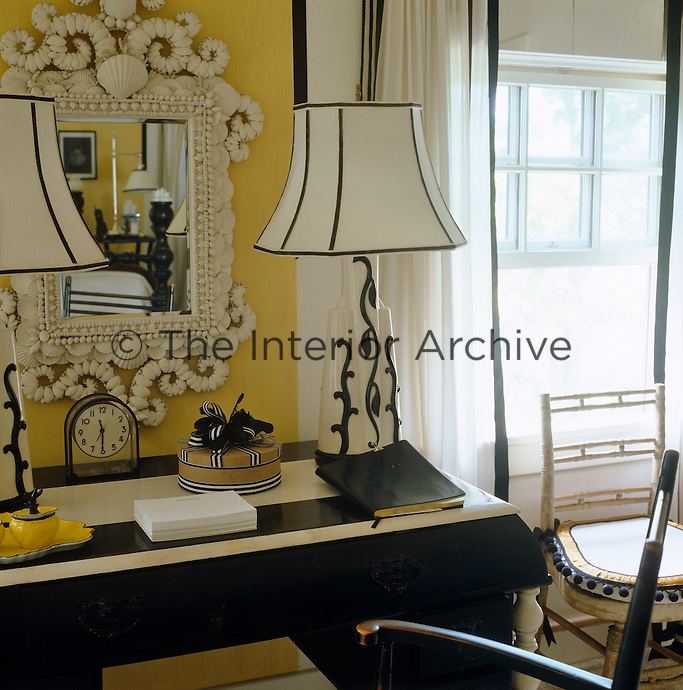 A pair of matching black and white lamps sit either side of a shell-encrusted mirror in this colour-coordinated bedroom