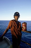 Rio de Janeiro, Brazil. Oil rig in the Campos Basin; man in dirty orange overalls and blue hard hat with tomato tin with paint