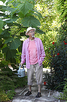 Mike Elliott Armitage, surrounded by plants in the garden that he created