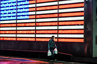 NEW YORK, NY - April 13:  A man walks with groceries at Times Square during a rainy day on April 13, 2020. in New York, United States. The global economy is facing the worst collapse since the WWII, while COVID-19  pandemic has now killed more than 22,000 people in the United States and at least 1,864,629 people died world wide.  (Photo by Eduardo MunozAlvarez/VIEWpress)