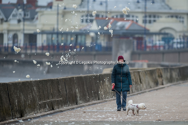 Wednesday  29 June 2016<br /> Pictured: A woman walks through the sea foam  in Porthcawl, South Wales <br /> Re: Rain and wind continues to batter parts of the UK