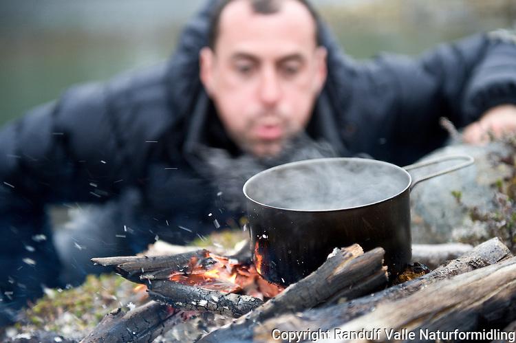 Mann puster på bål. ---- Man and camp fire.