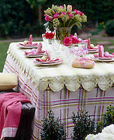 A table laid for a spring lunch in the garden with a scalloped green and white runner over a tartan tablecloth