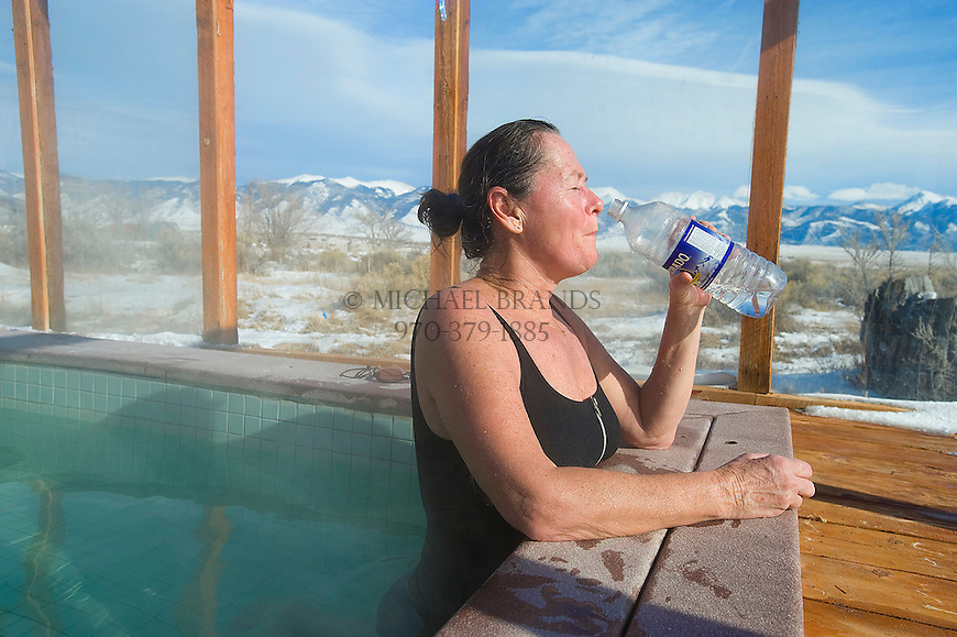 Diana Spence, of Salida, takes a sip of water while soaking at the Joyful Journey Hot Springs about 20-minutes outside Crestone, CO. The Sangre de Cristo mountain range is in the background. Michael Brands for The New York Times.