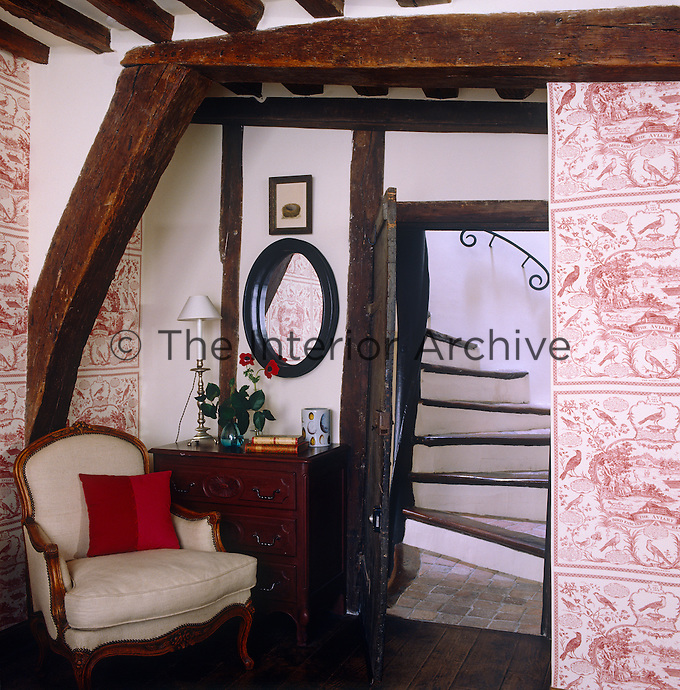 In a guest bedroom exposed oak beams and antique furniture create a charming and intimate corner