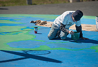 NWA Democrat-Gazette/BEN GOFF @NWABENGOFF<br /> Steve Abb works on a mural Thursday, March 8, 2018, on the basketball court at Olive Street Park in Rogers. The Runway Group partnered with Rogers Parks and Recreation to paint the mural titled 'Space Jam: Earth to Mars,' wich shows the Earth under one basket, Mars under the oposite and the moon at center court. Design and painting of the mural is being done by Graham Edwards Art and Abb Custom Painting, with Abb's son Mike Abb also working on the piece.