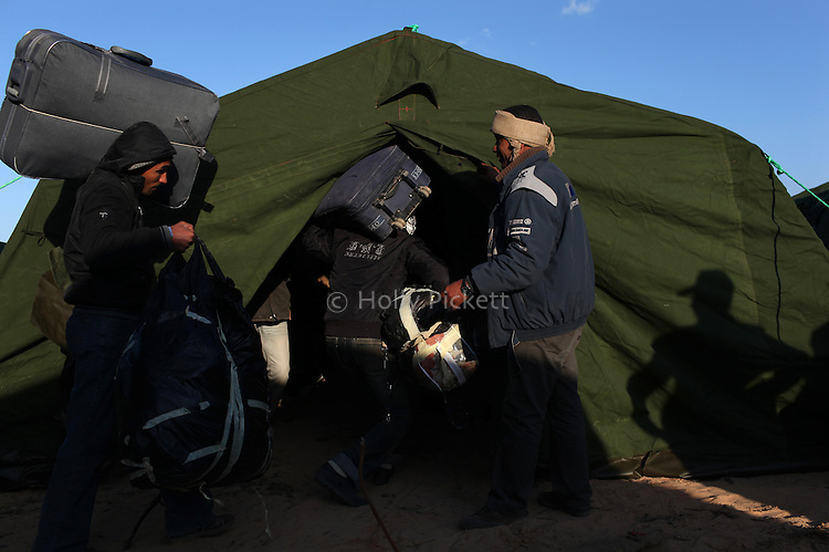 Foreign workers move their belongings into a tent at a temporary shelter at the Tunisia-Libya border near Ben Guerdane, Tunisia, Friday, Feb. 25, 2011. Thousands crossed the border into Tunisia, fleeing the violence of an uprising in Libya. Opposition forces reportedly have control of much of the country, but Col. Muammar Qaddafi still controls the capital Tripoli.