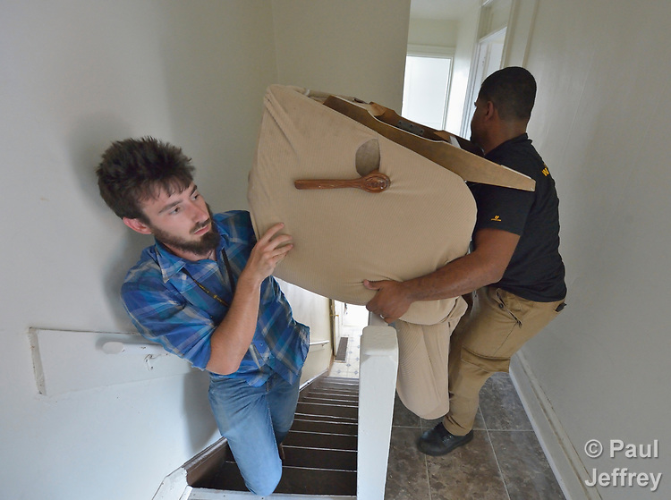 Josh Digrugilliers and Luis Ortiz carry a chair into an apartment in Lancaster, Pennsylvania. They are furnishing what will become home for a refugee family about to arrive in the United States. The two work for Church World Service, which resettles refugees in Pennsylvania and other locations in the United States. <br /> <br /> Photo by Paul Jeffrey for Church World Service.