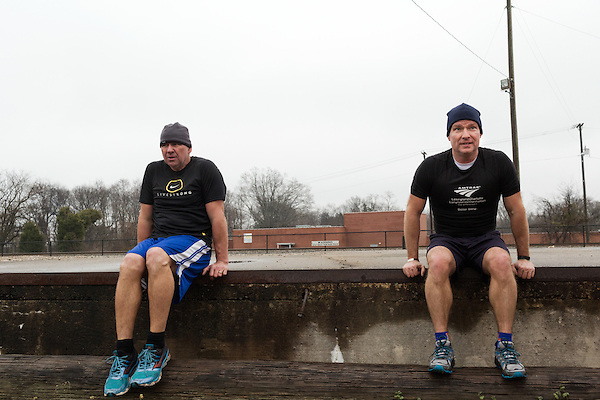 December 22, 2014. Lexington, North Carolina.<br />  Mayor Newell Clark, right, and his cousin Stan Lanier take a break during their hour long exercise routine around town.<br />   Newell Clark, the 43 year old mayor of Lexington, NC, leads a group of friends and colleagues on a 4 times a week exercise routine around downtown. The group uses existing infrastructure, such as an abandoned furniture factory, loading docks, stairs, and handrails to get fit and increase awareness of healthy lifestyles in a town more known for BBQ.<br /> Jeremy M. Lange for the Wall Street Journal<br /> Workout_Clark