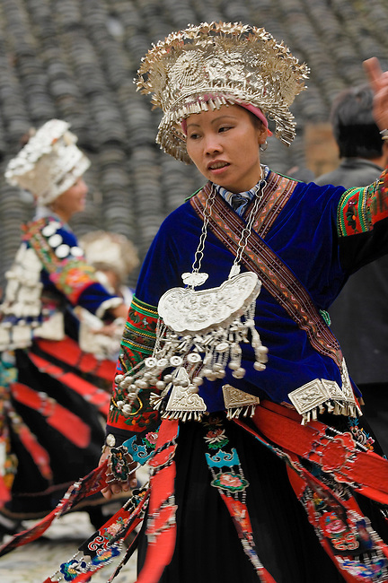 Lande is a Long-Skirt Miao Village. Young women wear silver crowns and distinctive breastplate-jewelry while spinning in traditional dance.