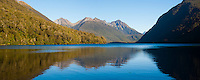 Panoramic Photo of the Reflection of Mountains in Lake Gunn, Fiordland, South Island, New Zealand. This panoramic photo shows the reflections of mountains in Lake Gunn, is a beautiful stop off point on the drive through Fiordland from Queenstown to Milford Sound. In comparison to the crowds of tourists at Milford Sound, Lake Gunn is a very peaceful and often provides stunning reflections of the mountains that surround the lake.