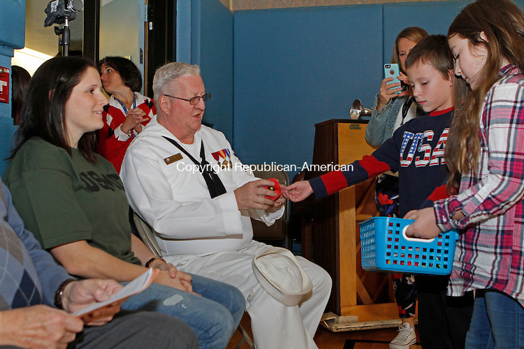 Southbury, CT-111116MK03 Navy veteran Scott Friend receives a poppy as Alexander Augustine and Marissa Tobet pass them out during the Veterans Day ceremony held at Pomperaug Elementary School on Friday Michael Kabelka / Republican-American.