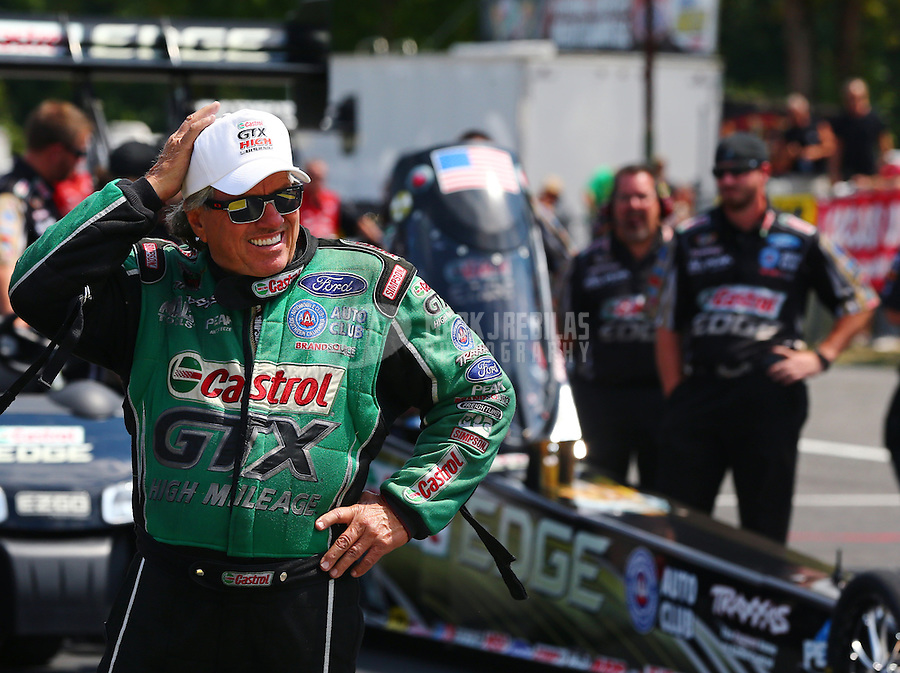 Aug. 2, 2014; Kent, WA, USA; NHRA funny car driver John Force stands alongside daughter Brittany Force and team during qualifying for the Northwest Nationals at Pacific Raceways. Mandatory Credit: Mark J. Rebilas-USA TODAY Sports