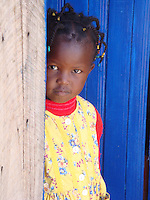 In Matanya, a small rural village near the base of Mount Kenya, in Kenya, East Africa, four year-old Wamuyu poses in a dress donated by Matanya's Hope non-profit based in the USA.  She is the youngest student in the Matanya's Hope sponsorship program. Blue is trademark for the color painted on a majority of doorways and shutters on houses in the area. The houses are made from timber, iron sheets, or a combination of Dung and Ash.