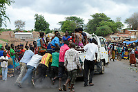 Zambia, Sinazongwe, rural market in village, men push a breakdown mini truck overloaded with women group / SAMBIA, Sinazongwe Distrikt, laendlicher Markt an einer Strasse im Dorf