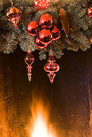 Detail of red baubles and spruce decorations over the roaring fire