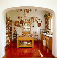 This large kitchen has a welcoming feel thanks to the deep red terracotta tiling and warm pine furniture