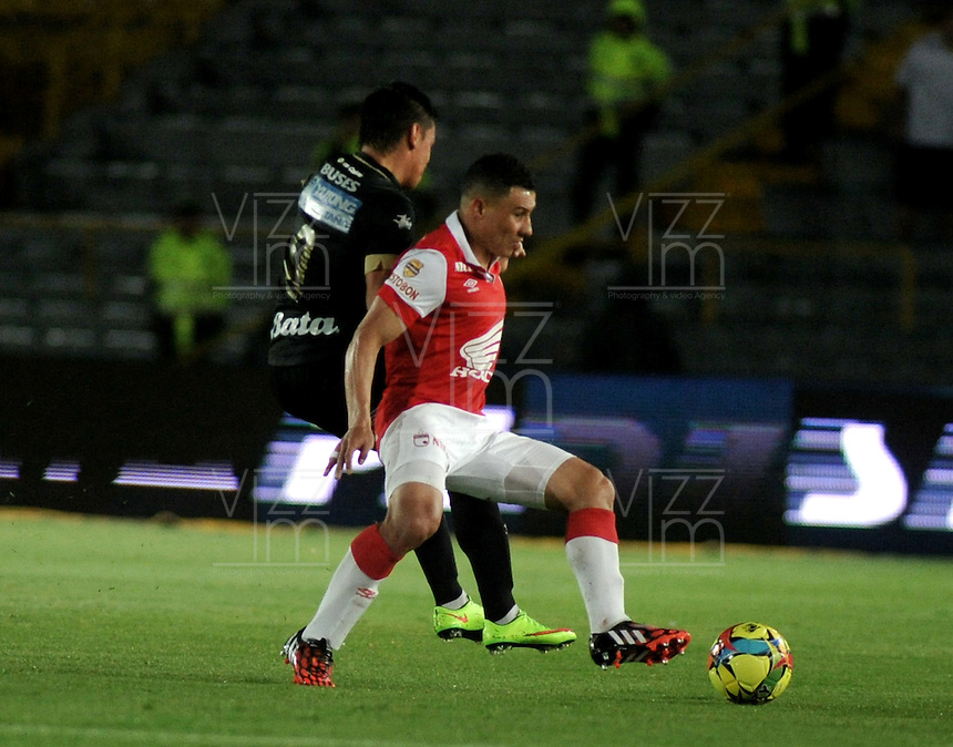 BOGOTA - COLOMBIA -18 -09-2014: Luis Arias (Der.) jugador de Independiente Santa Fe disputa el balón con Sergio Romero (Izq.) jugador de Once Caldas durante partido entre Independiente Santa Fe y Once Caldas por la fecha15 de la Liga Postobon II-2014, en el estadio Nemesio Camacho El Campin de la ciudad de Bogota. / Luis Arias (R) player of Independiente Santa Fe struggles for the ball with Sergio Romero ( (L) player of Once Caldas during a match between Independiente Santa Fe and La Equidad for the date 15 of the Liga Postobon II -2014 at the Nemesio Camacho El Campin Stadium in Bogota city, Photo: VizzorImage  / Luis Ramirez / Staff.