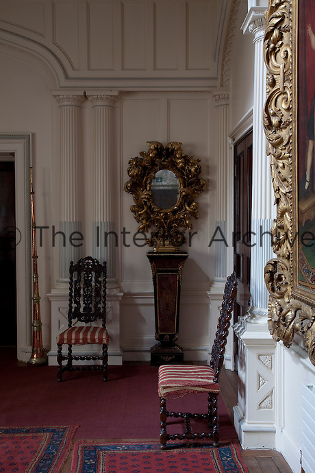 A pair of heavily carved gilt-framed mirrors on pedestals flanks the entrance to the staircase hall