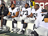 "Oakland Raiders offensive tackle Vadal Alexander (74), offensive tackle Marshall Newhouse (73) and offensive guard Gabe Jackson (66) sit on the bench and stare straight ahead as the national anthem is sung prior to the game against the Washington Redskins at FedEx Field in Landover, Maryland on Sunday, September 24, 2017.  The Raiders chose to demonstrate prior to their nationally televised contest following tweets earlier in the day from United States President Donald J. Trump urging owners to ""fire or suspend"" players who participated in the protests by not standing for the anthem.<br /> Credit: Ron Sachs / CNP"