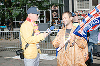 A reporter from The Brad Chadford show interviews a man wearing an inflatable dinosaur suit and holding a Trump 2020 flag in the Straight Pride Parade in Boston, Massachusetts, on Sat., August 31, 2019. The parade was organized in reaction to LGBTQ Pride month activities by an organization called Super Happy Fun America. The Brad Chadford Show is a youtube show.