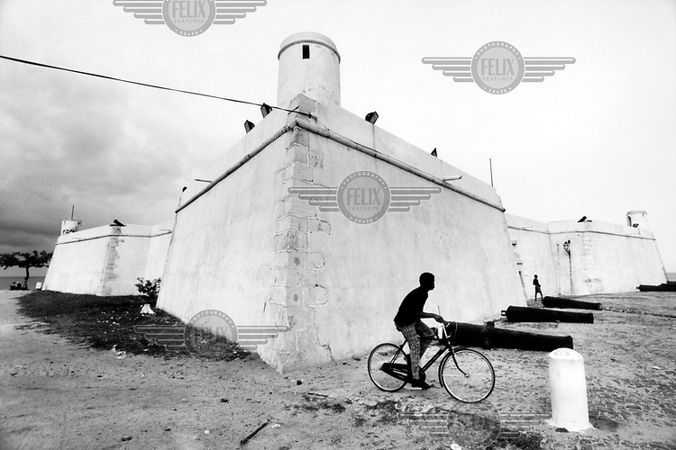 © Giacomo Pirozzi / Panos Pictures..SAO TOME..Boy cycling past a fort on the coast.