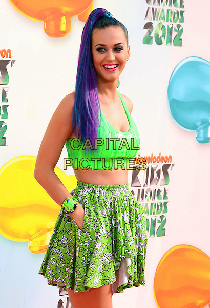 Katy Perry.2012 Nickelodeon Kids' Choice Awards held at the Galen Center, Los Angeles, California, USA, 31st March 2012..half length high blue dyed hair ponytail green bra crop cropped top print skirt midriff  hands in pockets white print smiling hands in pockets  purple .CAP/ADM.©AdMedia/Capital Pictures.