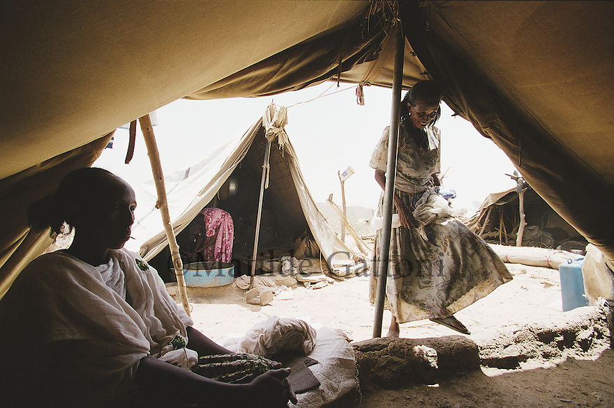Eritrea - Debub- Family sitting in their tent in an IDP camp. As a result of 30 years of war for independence against Ethiopia (from 1961 to 1991) and another 3 years from 1997 to 2000, there are 50,000 Eritreans currently living in internally displaced (IDP) camps throughout the country. These IDPs have fled three times in the last 10 years, each time because of renewed military conflict. They lived in relatives' homes when lucky enough, but mostly, the fled to the mountains, where they attempted to do what Eritreans do best, survive. Currently there is no Ethiopian occupation in Eritrea, but landmines prevent the IDPs from finally going home. .It is estimated that every Eritrean family lost two or three members to the war which makes the reality of the current emergency situation even more painful for Eritreans worldwide. Currently, the male population has been decreased dramatically, affecting the most fundamental socio-economic systems in the country. Among the refugee population, an overwhelming majority of families are female-headed, severely affecting agricultural production. For, IDPs in particular, 80% of households are female-headed..The unresolved border dispute with Ethiopia remains the most important drawback to Eritrea's socio-economic development, as national resources (human and material) continue to be prioritized for national defense. Eritrea is vulnerable to recurrent droughts and variable weather conditions with potentially negative effects on the 80 percent of the population that depend on agriculture and pastoralism as main sources of livelihood. The situation has been exacerbated by the unresolved border dispute, resulting in economic stagnation, lack of food security and increased susceptibility of the population to various ailments including communicable diseases and malnutrition..