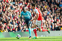 Modou Barrow of Swansea City  is chased by Laurent Koscielny of Arsenal during the Premier League match between Arsenal and Swansea City at Emirates Stadium on October 15, 2016 in London, England.