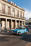 Havana, Cuba; a blue classic 1953 Studebaker driving down the Paseo de Marti in late afternoon sunlight