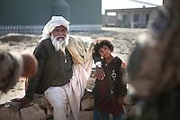 Afghanistan, 26.10.2011, Nawabad. Ein Afghane im Gespraeche mit einer gemeinsame Patrouille der Bundeswehr und afghanischer Armee in Nawabad. Die in Kundus stationierte 3. Task Force (ISAF) der Bundeswehr beginnt im Oktober 2011 die mehrtaegige Operation Orpheus. Durch Patrouillen in und um die Kleinstadt Nawabad (Dirstrikt Chahar Dareh) westlich von Kundus, Nordafghanistan, versuchen die rund 100 Infanteristen Rueckzugsorte Aufstaendischer unmoeglich zu machen. Unterstuetzt werden sie dabei durch einen Zug afghanischer Soldaten. An afghan man talks to a joint patrol of german Bundeswehr and Afghan National Army in Nawabad. In October 2011 Kunduz based 3.Task Force started a several days operation in and around Nawabad (District Chahar Dareh), west of Kunduz, northern Afghanistan. During the Operation Orpheus about 100 german infantry soldiers went out for patrols through the town and surrounding areas, which were expected as a retreat zone of insurgents. A platoon of afghan soldiers supports the german forces. © Timo Vogt/Est&Ost, NO MODEL RELEASE !!