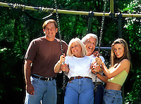 A smiling family - mature parents and teenage children playing on a swing.