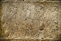 Assyrian relief sculpture panel of spearmen lining the road from the King Ashurnasirpal lion hunt.  From Nineveh  North Palace, Iraq,  668-627 B.C.  British Museum Assyrian  Archaeological exhibit no ME 120859
