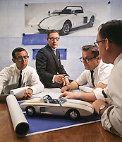 Ford Engineer Roy Lunn (center) and assistants Chuck Mountain (L), Ed Hull (middle R) and Jim Mason (R) study Ford Mustang 1 model, which they designed in 1962; their concept car inspired the Mustang that went into mass production in 1964. Ford Motor Company, Dearborn Michigan, 1966. Photo by John G. Zimmerman.