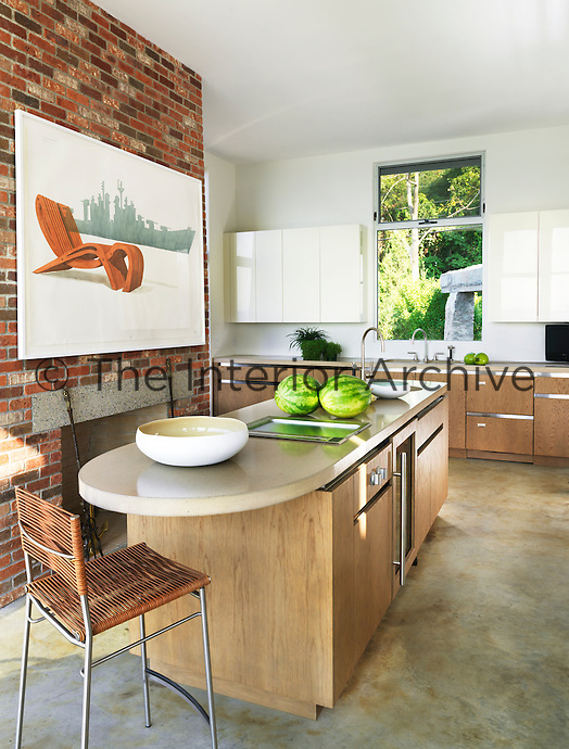 The spacious contemporary kitchen has a polished concrete floor, a central island and a fireplace set in a brick wall