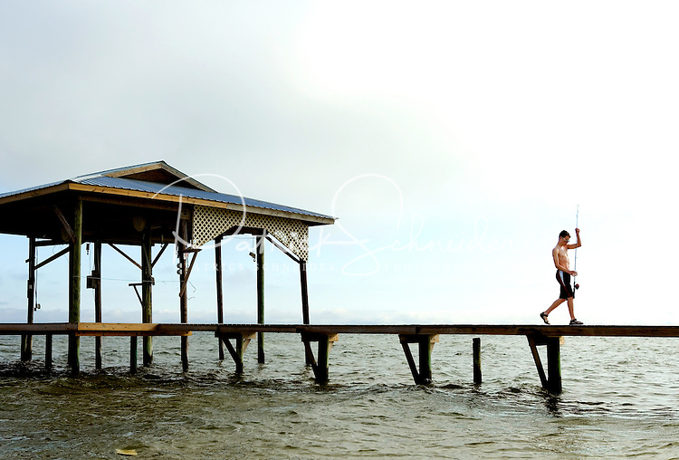 Two boys fish off a pier on Dauphin Island, Alabama, a barrier island located three miles south of the mouth of Mobile Bay in the Gulf of Mexico. This island, which is approximately 14 miles long and less than two miles wide, appears to have fully recovered from the impact of Hurricane Katrina (2005) and the BP Deepwater Horizon Oil Spill in 2010. Both events greatly reduced tourism income (fewer people came to the island) and local business owners say many establishments went out of business. Today they say they're looking forward to a rebounding tourism business.
