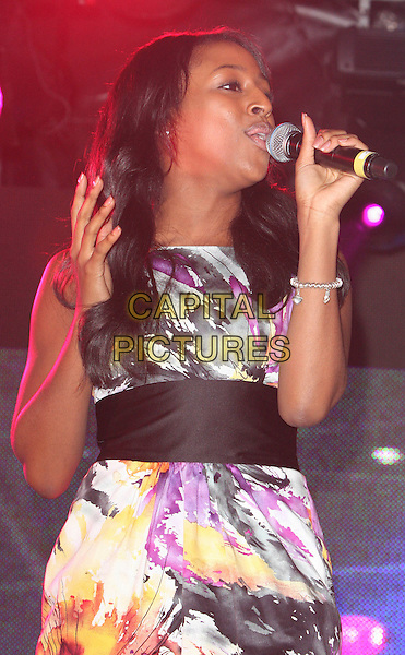 ALEXANDRA BURKE from X factor .Performing at the switching on of the Oxford Street Christmas Lights, London, England, November 12th 2008..half length live on stage concert gig water colour painted print dress black sash white pink .CAP/ROS.©Steve Ross/Capital Pictures