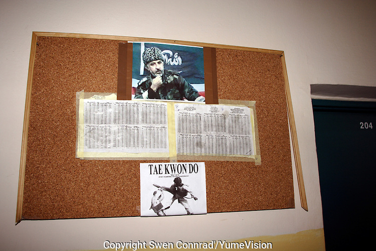 Billboard with the picture of the former President of Chechnya Aslan Maskhadov, killed by Russian Force in March 2005, the Ramadan pray timetable and the picture of Tae Kwon Do, to remember to not give up fighting for freedom. On the right, hotel room Nr. 204 of URiC Wola Center in Warsaw.