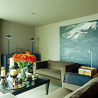 A large black and white painting is an arresting focal point in the living room and is displayed behind one of a matching pair of velvet-covered sofas designed by Michael Reeves
