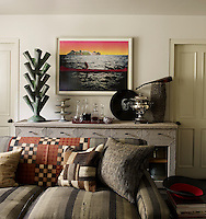 The Astuguevieille sideboard in the family room displays a Dutch tulipiere and the print is by Peter Doig