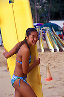 Teen surfer girl on Waikiki beach with surfboard