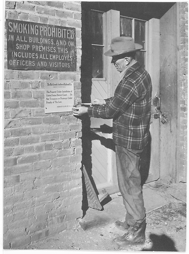 Ed Ranbow, roundhouse foreman, posting notice for receivership at Ridgway roundhouse.<br /> RGS  Ridgway, CO  ca 1948