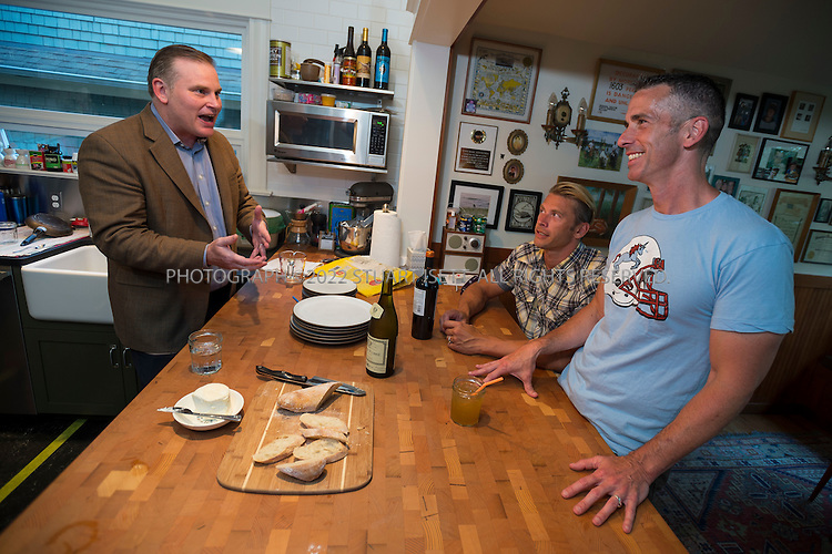 "8/15/2012--Seattle, WA, USA..A ""dining room debate"" between author, activist and sex advice columnist Dan Savage and National Organization for Marriage (NOM) president Brian Brown over same sex marriage...Here: Savage (right), his husband Terry Miller (center) and Brown (left) relax in the kitchen prior to dinner and the debate...After Savage criticized Christians and their interpretation of the Bible in a speech given at a Catholic high school, NOM president Brian Brown responded on Twitter by telling Savage to pick on someone his own size, and challenged him to a debate ""any time, anywhere"". So Savage invited Brown to debate in his Seattle home, where Savage was joined by his husband Terry Miller and their adopted son D.J. The debate was moderated by reporter Mark Oppenheimer...©2012 Stuart Isett. All rights reserved."