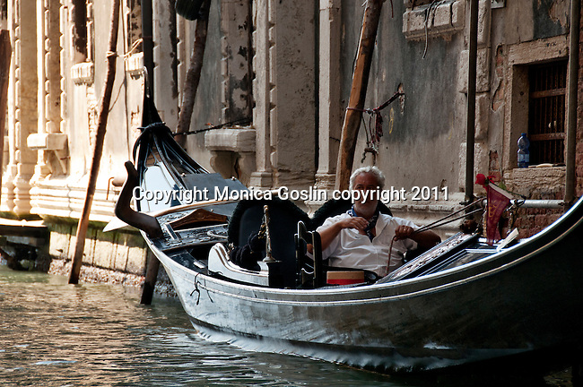 A gondolier takes a break in his gondola in Venice, Italy