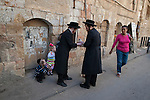 A woman walks next to a people who practice 'Kaparot', in the ultra-orthodox Jewish neighborhood of Me'a She'arim in Jerusalem. 'Kaparot' is a ritual practiced on the eve of Yom Kippur (Day of Atonement), which consists of swinging a chicken overhead three times before slaughtering it and later donating it to charity, an act believed to serve as a form of atonement.